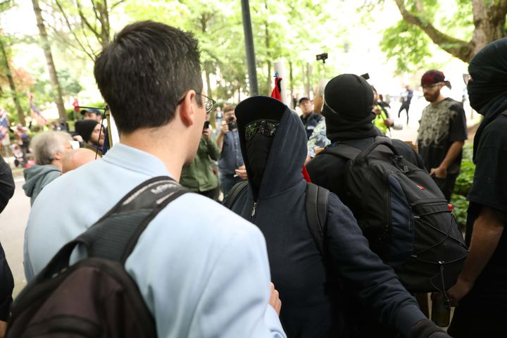 Brian Fife, a prominent far-right figure, is confronted by Black Bloc protesters on Sunday in Portland, Oregon.