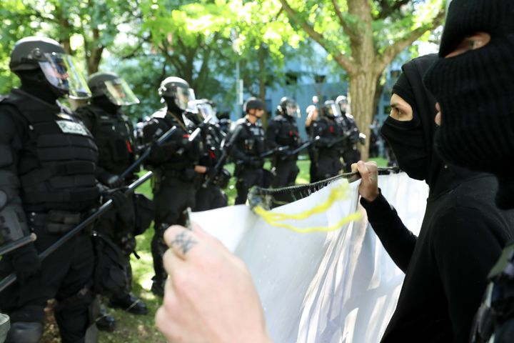 Black-clad protesters in Portland, Oregon, faced off against officers who kept them separated from pro-Trump demonstrators.
