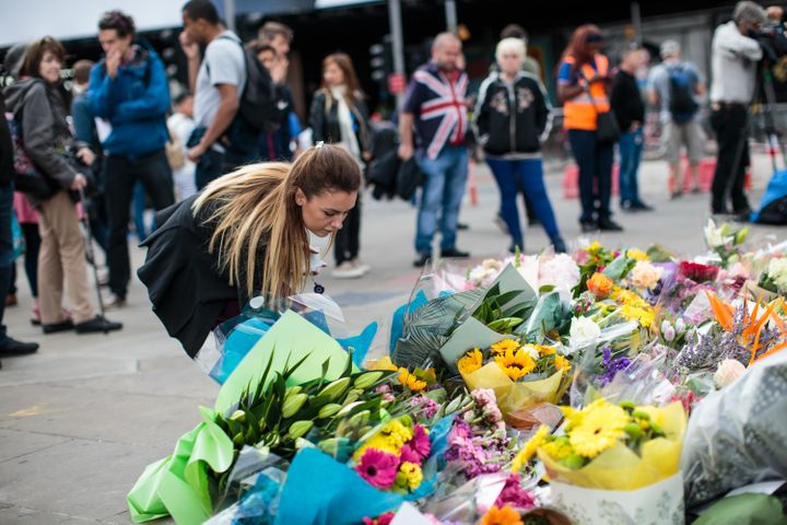 A woman lays flowers among other floral tributes left on London Bridge following the June 3rd terror attack on June 5, 2017 i