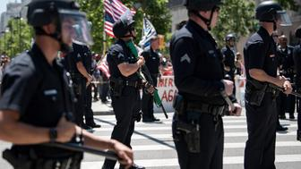 Los Angeles police officers standing between Trump supporters and the May Day protestors in Los Angeles, California on May 1, 2017. Activists marked the International Workers' Day with rallies in support of rights for workers and immigrants, as well as opposition to Presidents Donald Trump.  (Photo by Ronen Tivony/NurPhoto via Getty Images)