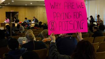 FLINT, MICHIGAN - FEBRUARY 3:  A woman in a crowd of local residents holds up a hand made sign as she attends a city council meeting at Flint City Hall on Wednesday, February 3, 2016. The meeting introduced a discussion about whether residents should have to pay for their water bills and how funds should be allocated to take on the costs. (Photo by Brittany Greeson for The Washington Post via Getty Images)
