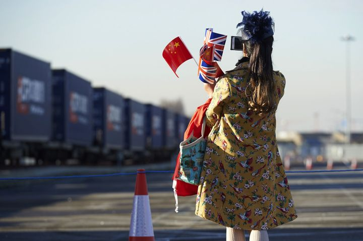 A woman holds Chinese and British flags as she watches the first freight train to travel from China arrive in London's Barkin