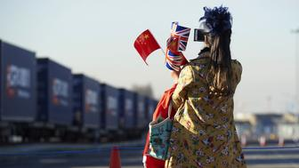 A woman holds Chinese and Union flag as she takes a photo of a freight train laden with goods from China, at DB Cargo's London Eurohub rail freight depot in Barking, east London on January 18, 2017, after it arrived from Yiwu in the eastern Chinese province of Zhejiang. After a journey of 18 days and 12,000 kilometers, the first freight train directly connecting China to the United Kingdom arrived on Wednesday in London. The journey demonstrates Beijing's desire to strengthen its commercial links to Western Europe by reviving the ancient Silk Road, which was used to transport precious merchandise to the Old Continent. / AFP / NIKLAS HALLE'N        (Photo credit should read NIKLAS HALLE'N/AFP/Getty Images)