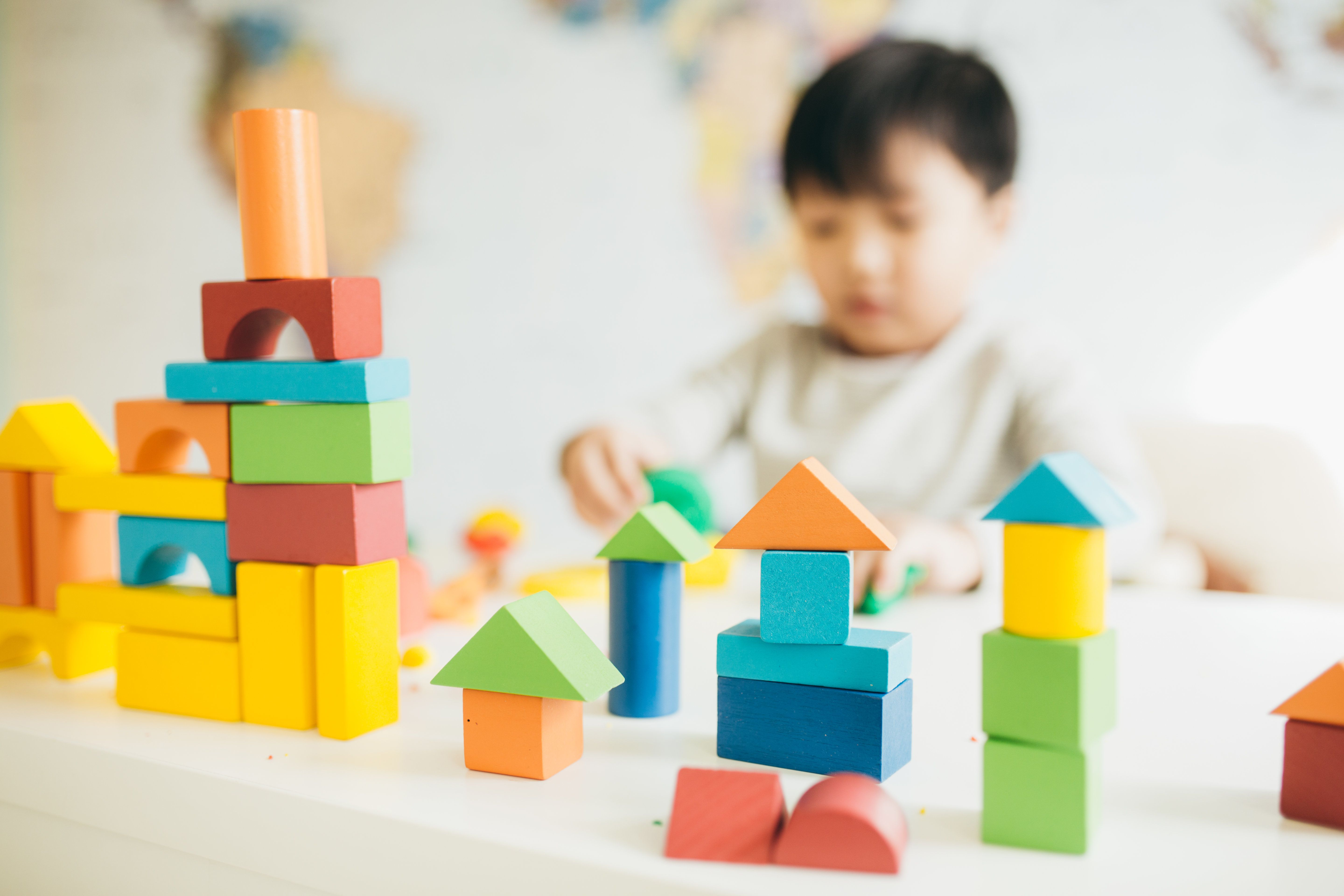 Focus on  wooden blocks and child on background