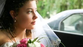 Face of bride looking from the car window with bunch of white and pink roses   Note to inspector: the image is pre-Sept 1 2009
