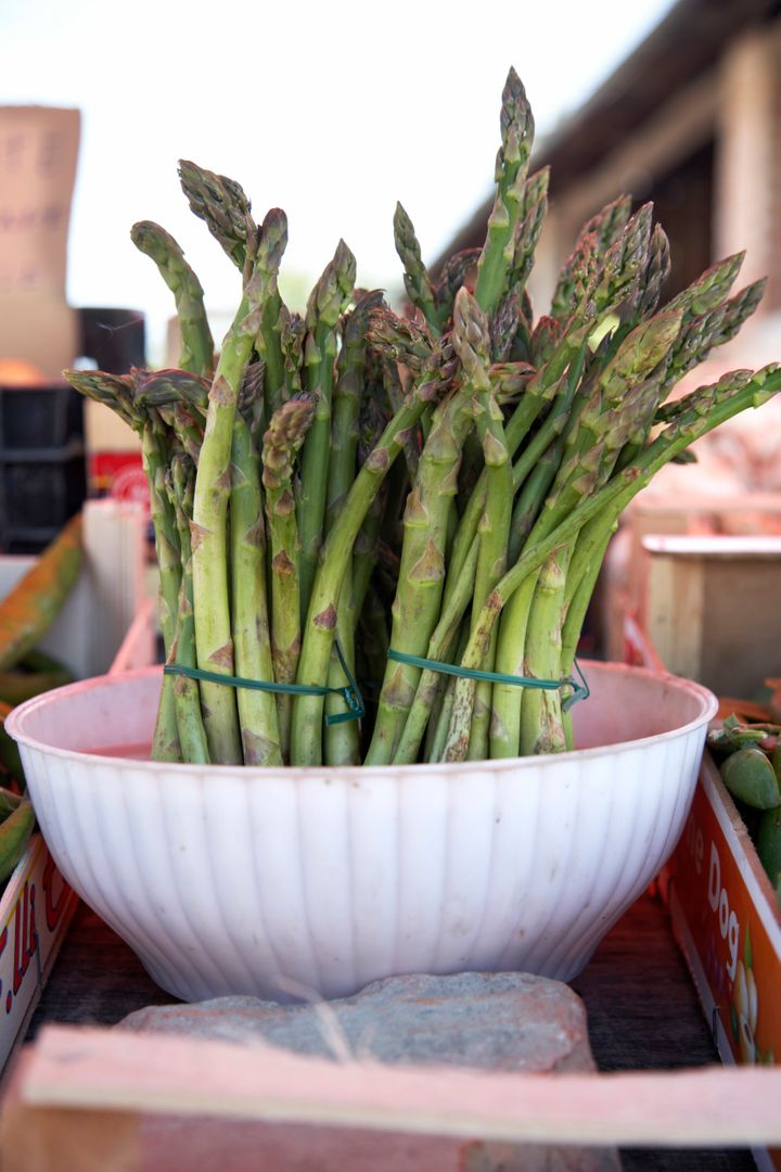 A bunch of fresh asparagus stored in a bowl of water.