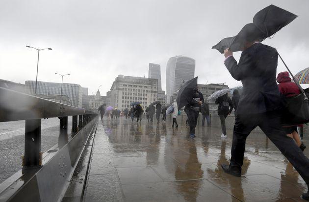 Pedestrians battle the elements in London on