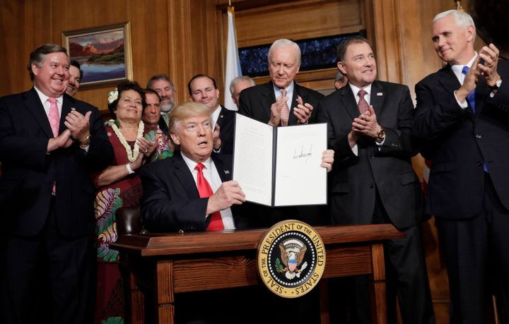 President Donald Trump holds up his executive order directing a review of previous national monument designations during