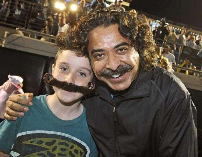 Jacksonville Jaguars owner Shahid Kahn embraces a prospective Mustached American fan