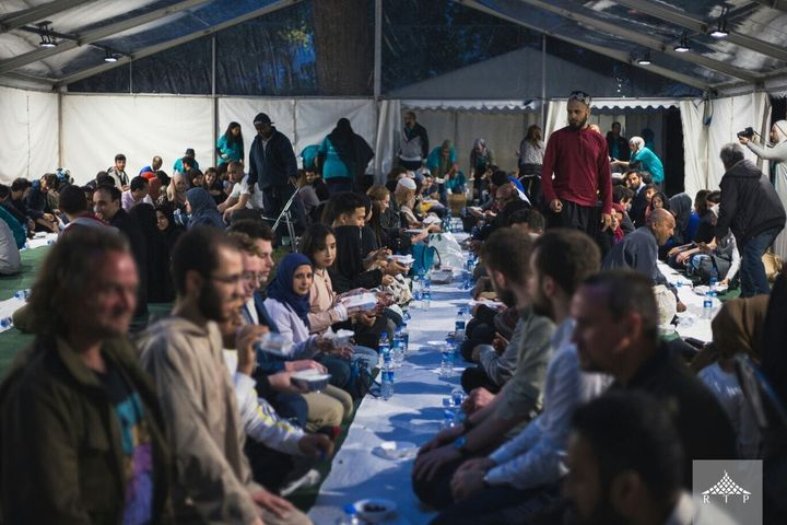 At an Open Iftar event, people of different faiths, races, and backgrounds eat a meal together.