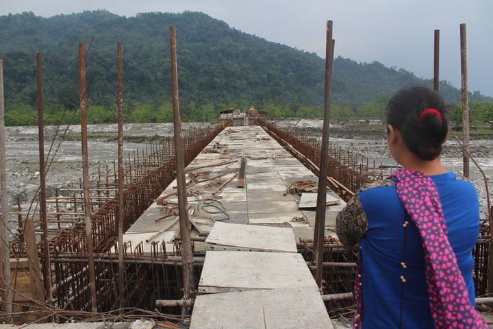 A Idu lady looks at the unfinished Dipu Nallah bridge, with Tezu on the other side.