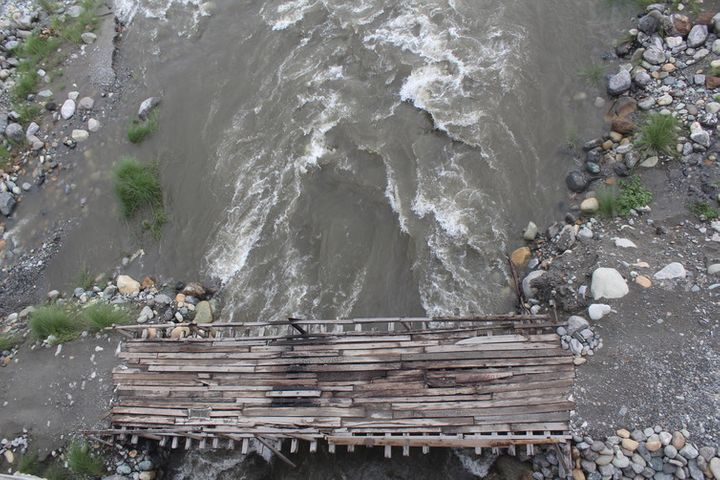Makeshift wooden plank bridges for motorbikes to cross parts of the braided Dipu Nallah river in the dry season.