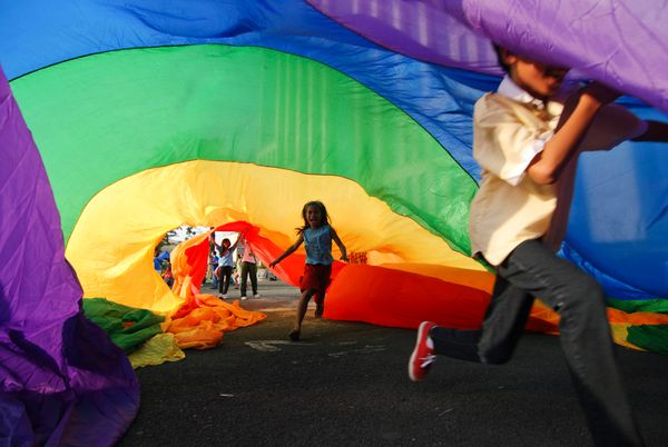 A boy plays under a rainbow flag during the Manila Gay Pride march on December 8, 2012 in Makati, Philippines. (Photo b