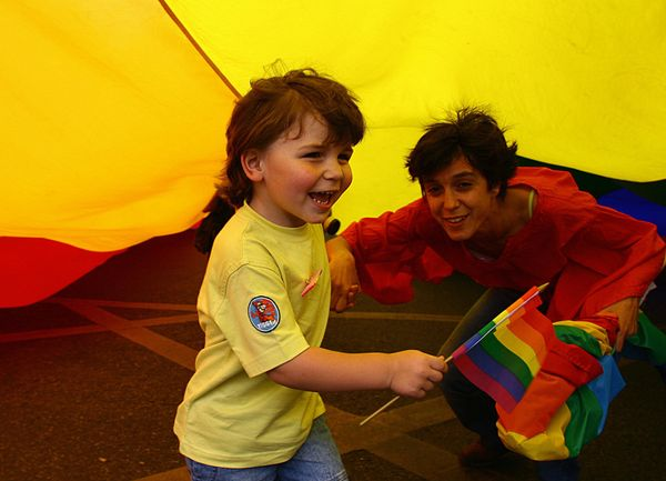A mother and child play under a giant rainbow flag during the Gay Pride parade in downtown Lisbonon June 24,2006.