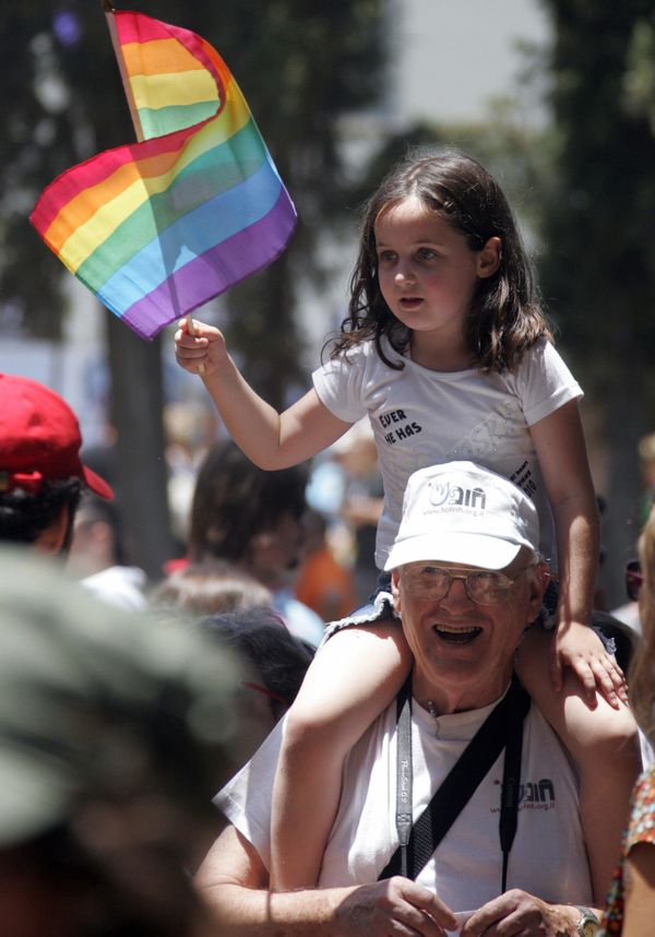 An Israeli girl sits on a relative's shoulders waving the rainbow flag, the international symbol of gay pride, during the ann