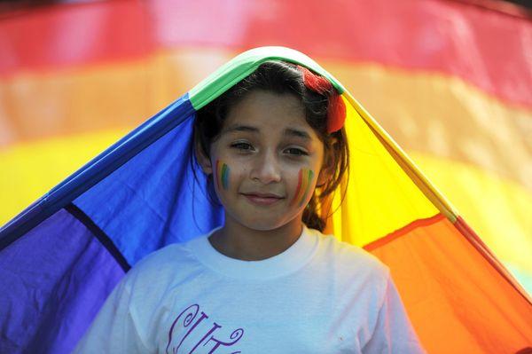 A young girl smiles during a Gay Pride parade along Roosevelt Avenue in San Salvador on June 29, 2013. AFP PHOTO/Jose CABEZAS