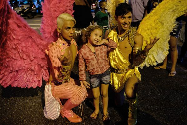 Revelers pose for a picture with a young girl during the 2nd LGBT Pride parade at Alemao favela in Rio de Janeiro, Brazil, on