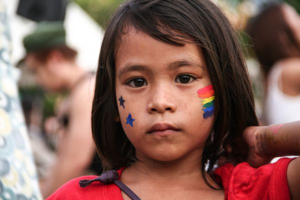 A young kid with a rainbow flag face paint poses for the camera at the Rizal Park in Manila. Thousands of LBGTQ members march