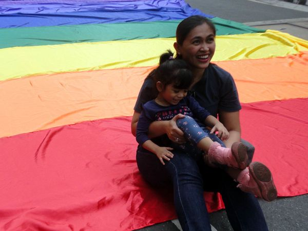 A Filipino woman sits on a rainbow flag with her child during a Gay Pride event in Quezon City, east of Manila, Philippines,