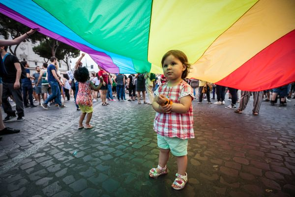 A child plays under a giant rainbow flag, a symbol of the gay rights movement, as she takes part in the 22nd annual Gay Pride