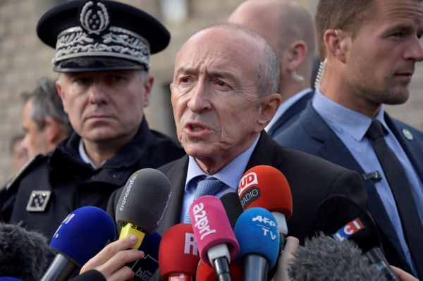 French Minister of the Interior Gerard Collomb (C) addresses media representatives near the site of an attack at the entrance