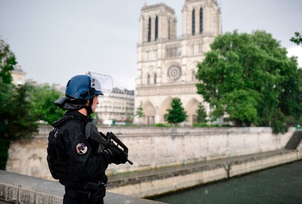 A French police officer holds a weapon as he stands near the entrance of Notre Dame Cathedral.