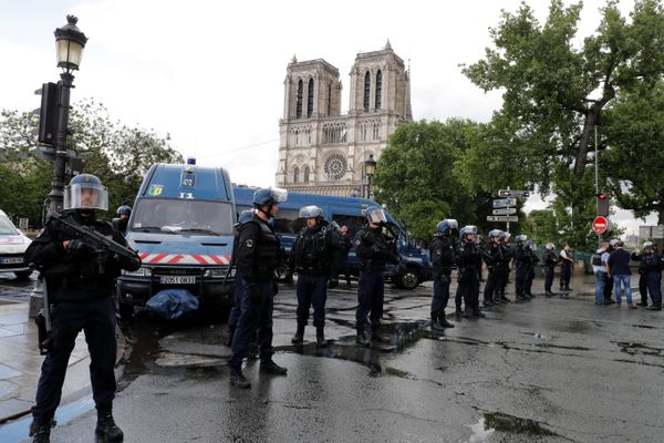French police stand at the scene of a shooting incident near the Notre Dame Cathedral.