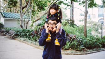 Lovely toddler girl sitting on dad's shoulders while both smiling joyfully in the park.