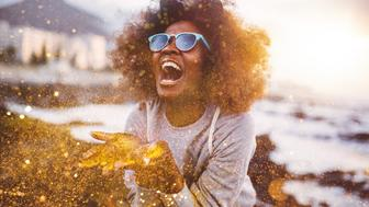Laughing Afro hipster girl having fun throwing gold glitter from her hands while at tthe beach at sunset