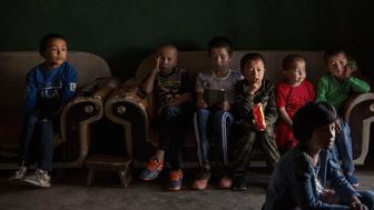 TURPAN, CHINA - SEPTEMBER 12:  (CHINA OUT) Uyghur children watch a television program on the morning of the Corban Festival on September 12, 2016 in Turpan County, in the far western Xinjiang province, China. The Corban festival, known to Muslims worldwide as Eid al-Adha or 'feast of the sacrifice', is celebrated by ethnic Uyghurs across Xinjiang, the far-western region of China bordering Central Asia that is home to roughly half of the country's 23 million Muslims. The festival, considered the most important of the year, involves religious rites and visits to the graves of relatives, as well as sharing meals with family. Although Islam is a 'recognized' religion in the constitution of officially atheist China, ethnic Uyghurs are subjected to restrictions on religious and cultural practices that are imposed by China's Communist Party. Ethnic tensions have fueled violence that Chinese authorities point to as justification for the restrictions.  (Photo by Kevin Frayer/Getty Images)
