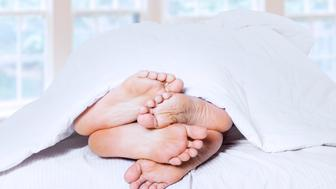 Close-up of couple's feet cuddling. shost at bedroom