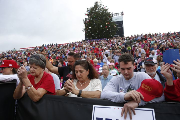 Members of the audience pray while waiting to listen to U.S. President-elect Donald Trump speak during a USA Thank You Tour e