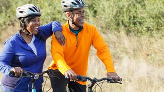 A mature, African American couple riding mountain bikes in a state park. They are wearing helmets, standing side by side with the woman leaning her arm on his shoulder. They are watching something, laughing.