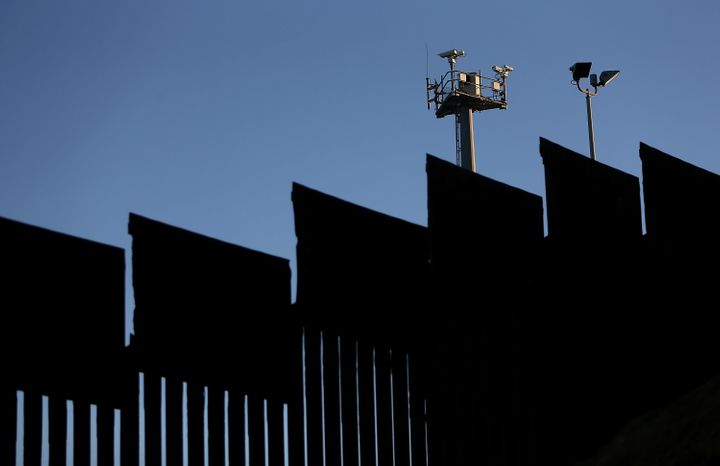 Surveillance cameras tower above the U.S.-Mexico border fence at Playas de Tijuana in Tijuana, Mexico.
