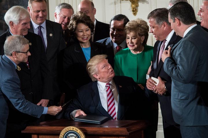President Donald Trump at his tiny desk signs a memo to Congress outlining his plan to privatize the nation's air traffic con