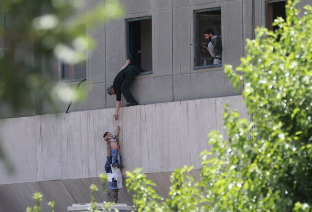 A boy is evacuated during an attack on the Iranian parliament in central Tehran, Iran, June 7,