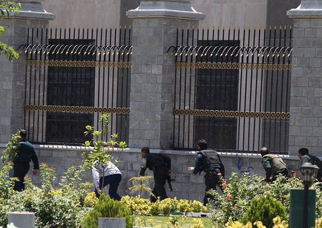 Members of Iranian forces run during an attack on the Iranian parliament in central Tehran, Iran, June...
