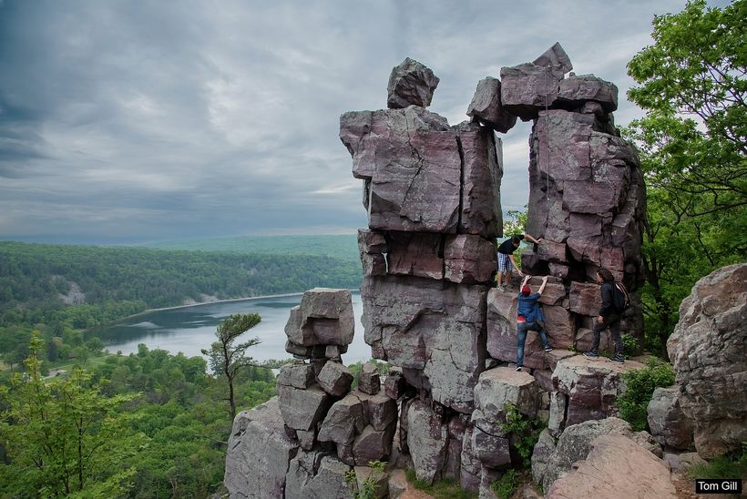 A group of hikers climbing into Devil's Doorway.