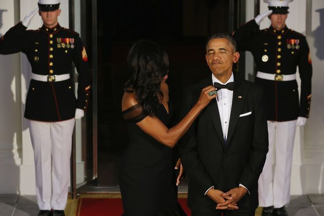 First Lady Michelle Obama straightens U.S. President Barack Obama's tie while they wait on the North...