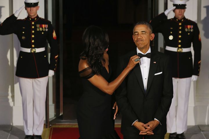First Lady Michelle Obama straightens U.S. President Barack Obama's tie while they wait on the North Portico for the arrival of Chinese President Xi Jinping and his wife Madame Peng Liyuan ahead of a state dinner at the White House September 25, 2015 in Washington, DC.