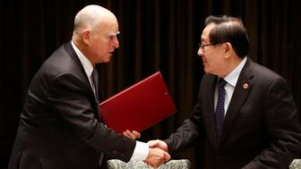 California Governor Jerry Brown and Chinese Minister of Science and Technology Wan Gang attend a signing ceremony at the International Forum on Electric Vehicle Pilot Cities and Industrial Development in Beijing, China June 6, 2017.   REUTERS/Thomas Peter