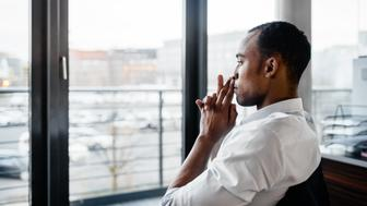 Pensive and serious young black businessman sitting in a chair in his office and looking through a window away. Shot from behind.