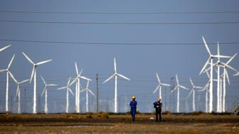Workers walk near wind turbines for generating electricity, at a wind farm in Guazhou, 950km (590 miles) northwest of Lanzhou, Gansu Province September 15, 2013.  China is pumping investment into wind power, which is more cost-competitive than solar energy and partly able to compete with coal and gas. China is the world's biggest producer of CO2 emissions, but is also the world's leading generator of renewable electricity. Environmental issues will be under the spotlight during a working group of the Intergovernmental Panel on Climate Change, which will meet in Stockholm from September 23-26. Picture taken September 15, 2013. REUTERS/Carlos Barria  (CHINA - Tags: ENERGY BUSINESS ENVIRONMENT)