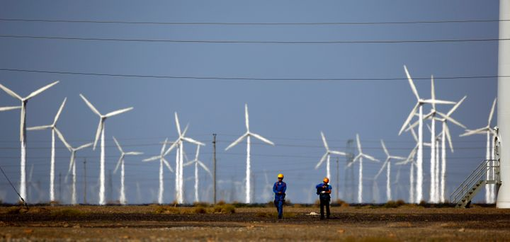 Workers walk near wind turbines for generating electricity, at a wind farm in Guazhou, China.