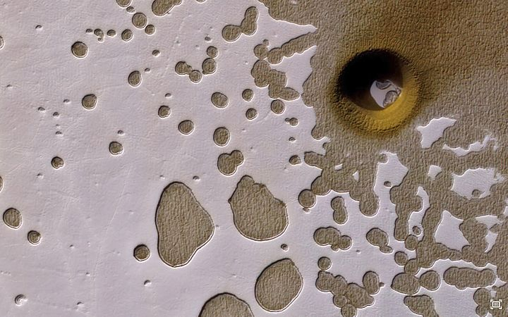 "This strange, nearly perfectly circular feature in a ""Swiss Cheese"" area of Mars has scientists wondering if"