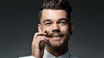 happy young man touching moustache