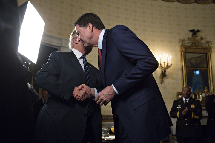President Donald Trump, left, warmly greets then-FBI Director James Comey in January. Comey claims Trump pressured him over t
