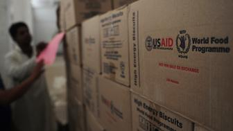 In this picture taken on November 2, 2012, a Pakistani worker arranges aid supplies at the World Food Programme (WFP) supply centre at Mirali Village in Jacobabad district, around 500 kilometres (300 miles) north of the metropolis of Karachi. While the United States recovers from superstorm Sandy, away from the glare of the international media, five million Pakistanis are struggling to get by in the country's third successive year of massive floods.  Two years after the worst floods in Pakistan's history captured the world's attention, this summer's monsoon rains once again inundated huge areas of the Indus Valley, with rural parts of Sindh province the worst hit.  AFP PHOTO/Rizwan TABASSUM        (Photo credit should read RIZWAN TABASSUM/AFP/Getty Images)