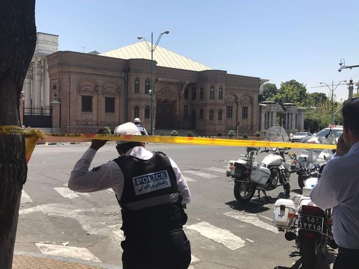 Police take security measures at the scene after gunmen opened fire at Iran's parliament and at the shrine of Ayatollah Ruhol