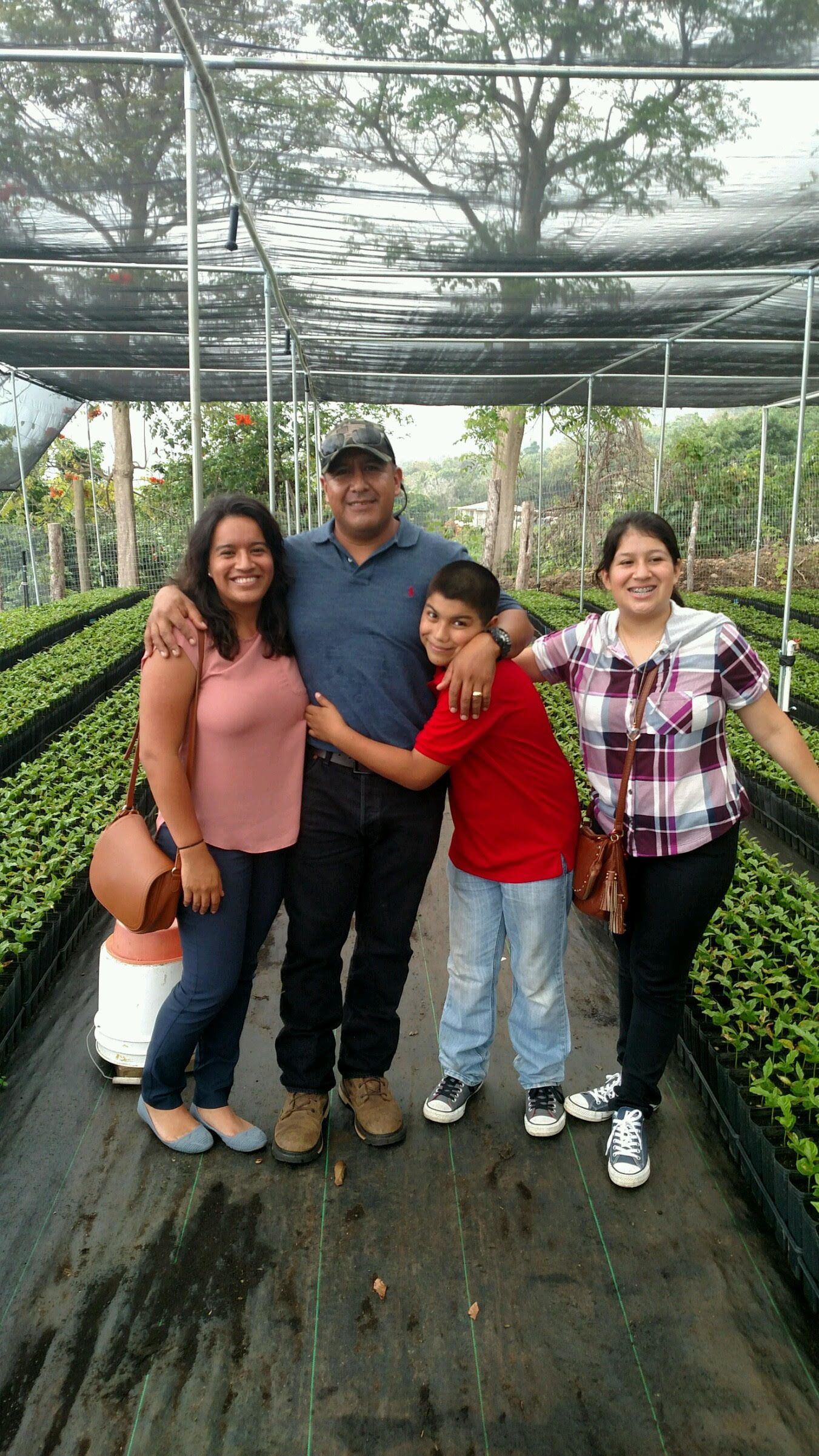 Andres Magana and his three children pose in one of a coffee bean processing plant in Hawaii